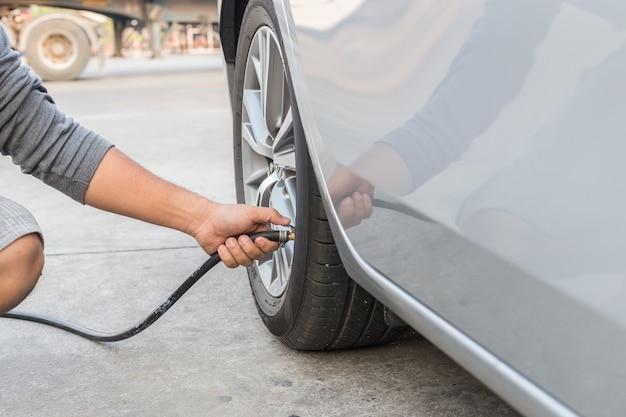 Uomo che controlla la pressione dell'aria e riempiendo l'aria con le gomme della sua auto
