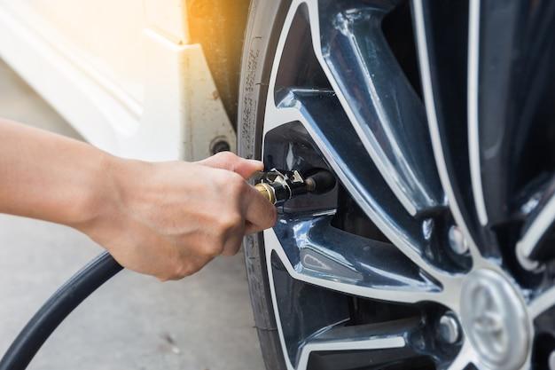 Uomo che controlla la pressione dell'aria e riempiendo l'aria nei pneumatici della macchina. foto di concetto