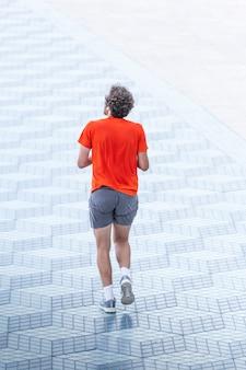 Uomo che corre in uno spazio solitario, concetto minimalista, solitudine, sforzo, realizzazione, superamento