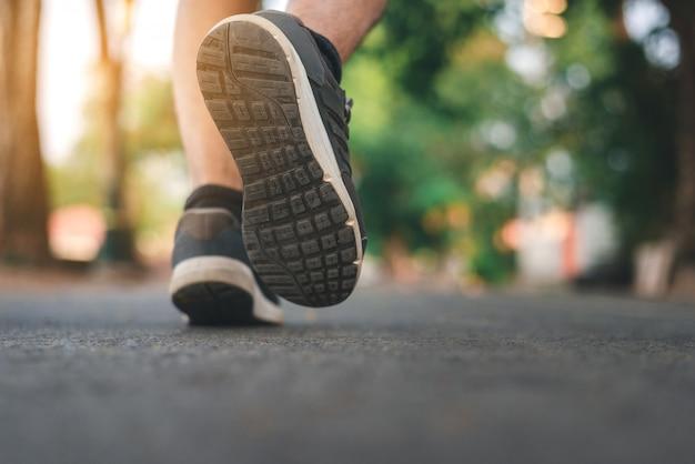 Uomo che corre sul parco con close up scarpe
