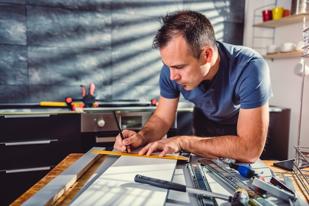 Uomo che costruisce mobili da cucina