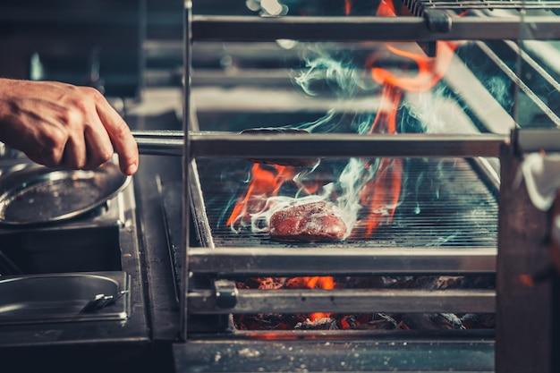 Uomo che cucina carne alla griglia