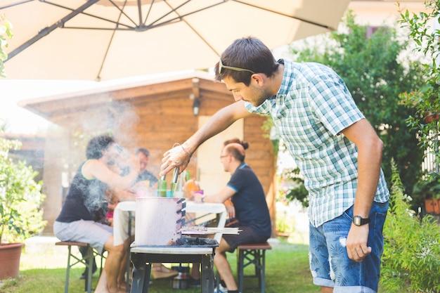 Uomo che cucina carne sul barbecue