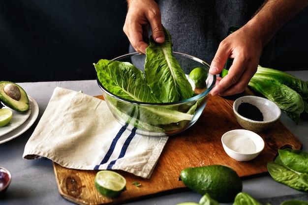 Uomo che cucina insalata verde della lattuga romana dell'insalata della disintossicazione