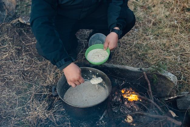 Uomo che cucina porridge delizioso all'aperto