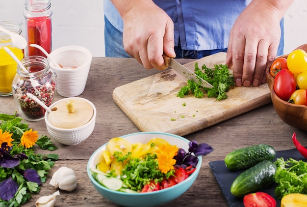Uomo che cucina un'insalata vegetariana