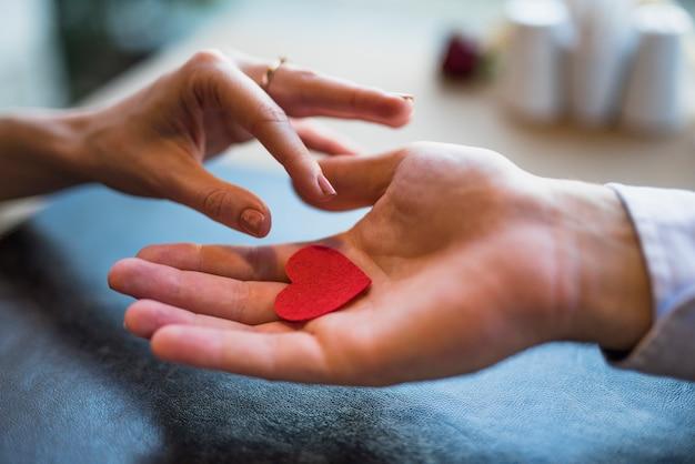 Uomo che dà il cuore rosso dell'ornamento alla donna