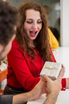 Uomo che dà il piccolo contenitore di regalo bianco alla donna