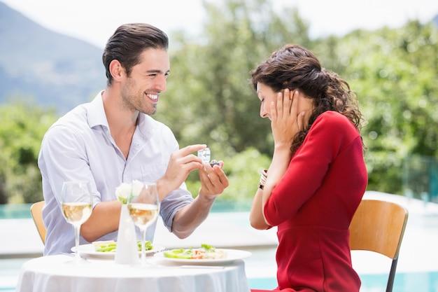 Uomo che dà l'anello di fidanzamento alla donna stupita