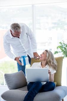 Uomo che dà regalo al computer portatile della tenuta della donna