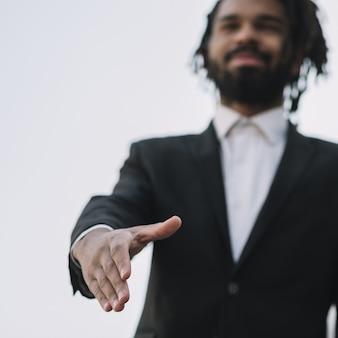 Uomo che dà scossa della mano angolo basso