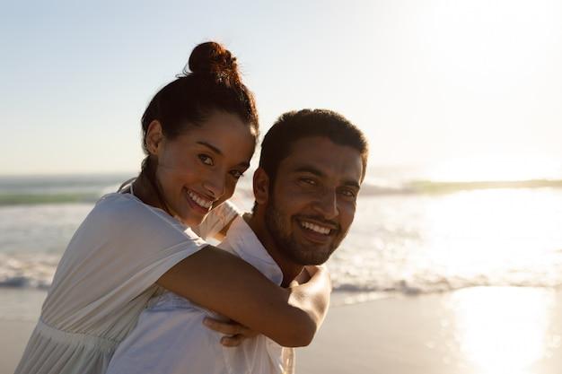 Uomo che dà sulle spalle giro alla donna sulla spiaggia