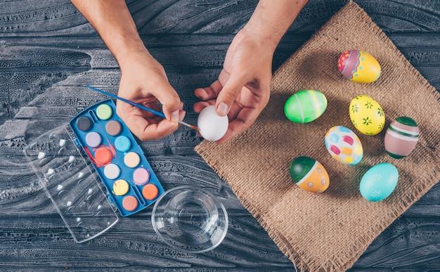 Uomo che dipinge un uovo con le uova di pasqua sul sacco e dipingere vista dall'alto su fondo di legno scuro