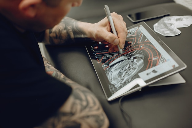 Uomo che disegna lo schizzo in una compressa