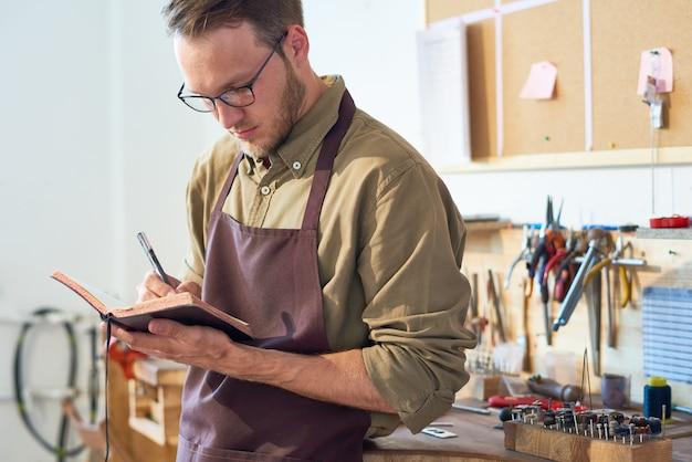 Uomo che disegna schizzi in officina