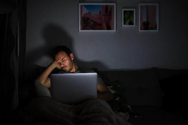 Uomo che dorme con il computer acceso
