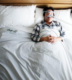 Uomo che dorme con una maschera anti-russamento