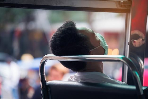 Uomo che dorme dopo essere stato processato da un duro lavoro in omnibus pubblico di bangkok a bangkok, in tailandia