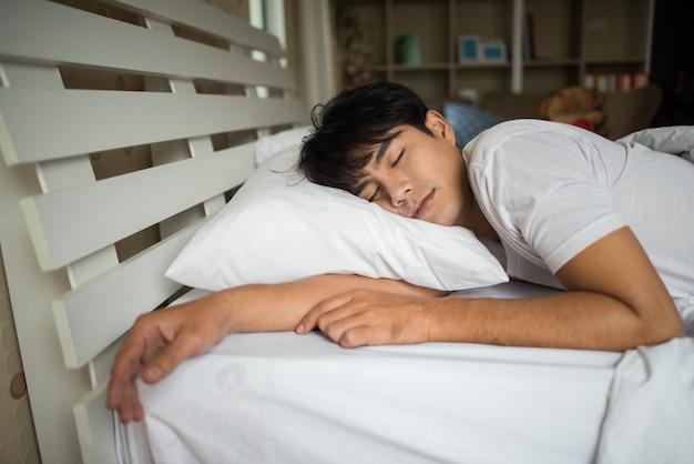 Uomo che dorme sul letto al mattino