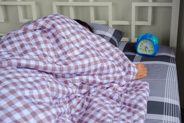 Uomo che dorme sul letto.