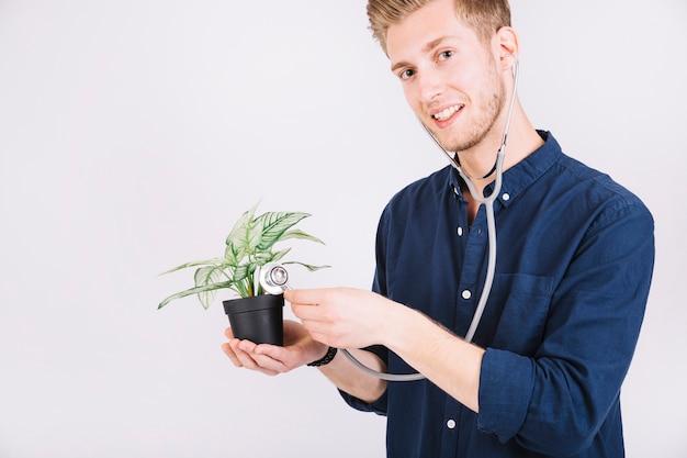 Uomo che esamina la pianta in vaso con lo stetoscopio