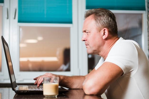 Uomo che esamina la vista laterale del computer portatile
