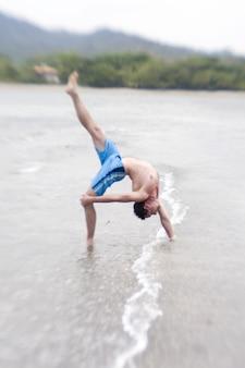 Uomo che fa backbend sulla spiaggia
