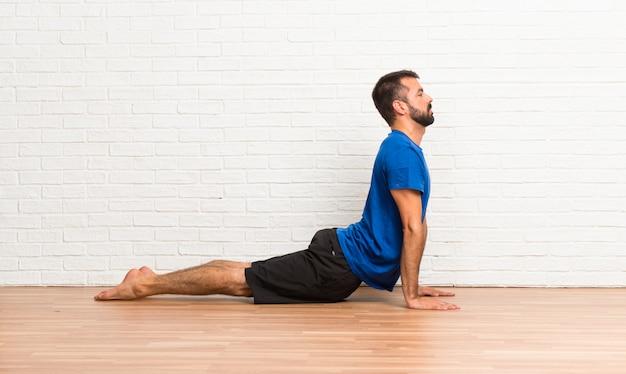 Uomo che fa esercizi di yoga al chiuso