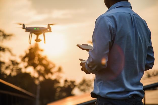 Uomo che fa funzionare un drone con telecomando, pilotaggio di droni al tramonto