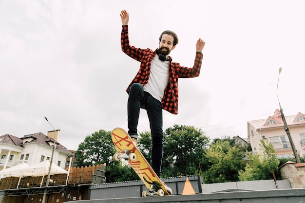 Uomo che fa i trucchi allo skate park