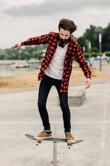 Uomo che fa i trucchi con lo skateboard