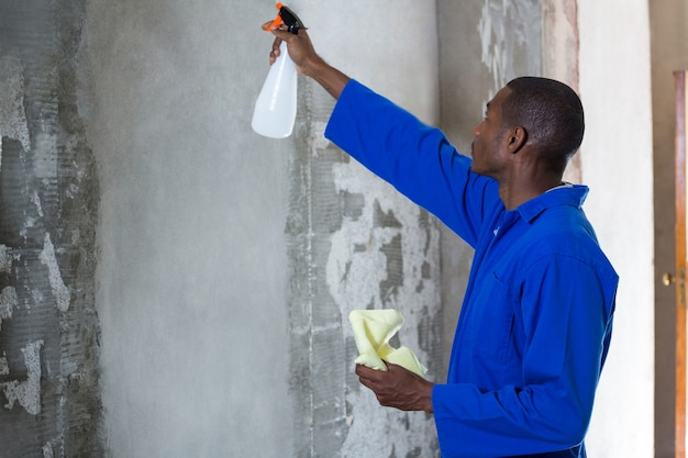 Uomo che fa il controllo dei parassiti su una parete