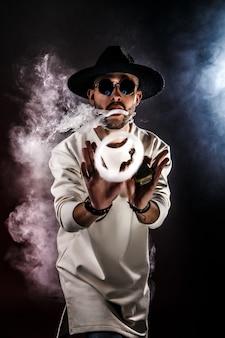 Uomo che fa l'anello di fumo con vape