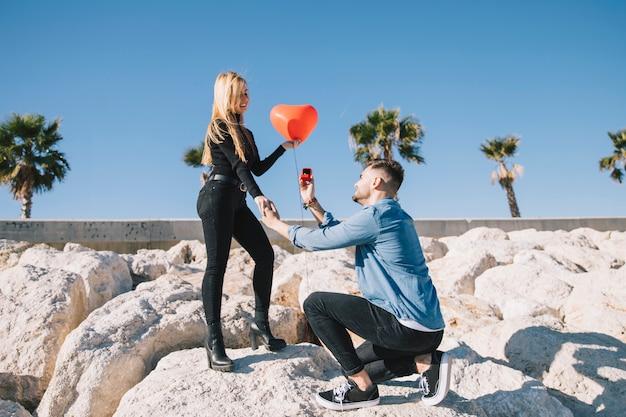 Uomo che fa la proposta alla fidanzata sulla riva
