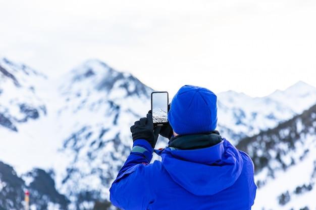 Uomo che fa le foto con il suo telefono nella neve