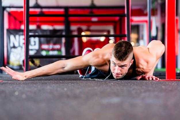 Uomo che fa push-up in palestra fitness sportivo