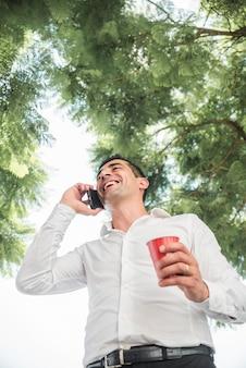 Uomo che fa telefonata sotto l'albero