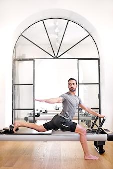 Uomo che fa un allungamento in piedi affondo pilates