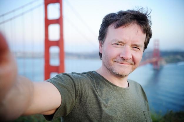 Uomo che fa un autoritratto (selfie) con il famoso golden gate bridge a san francisco, california, usa