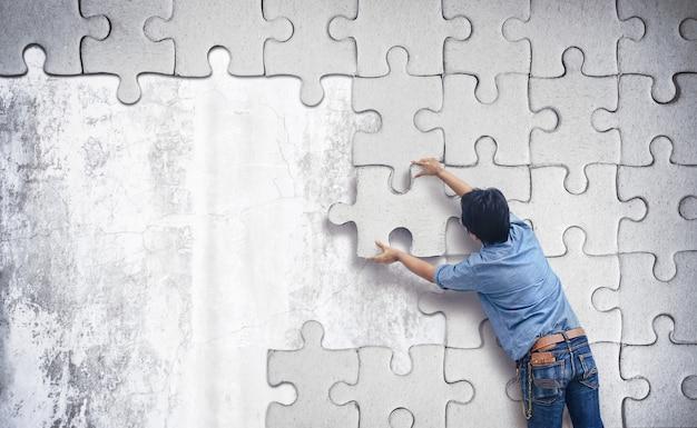 Uomo che fa un puzzle sul muro.