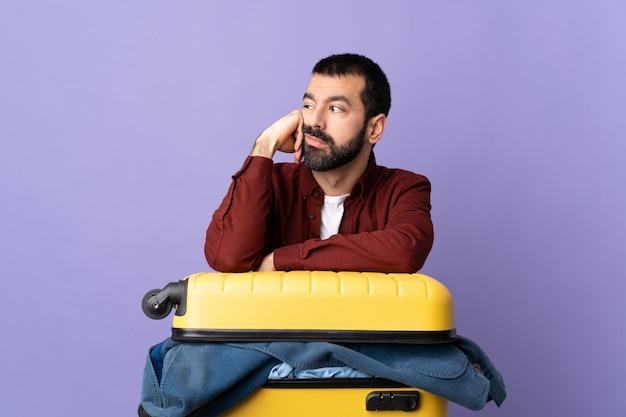 Uomo che fa valigia sopra la parete isolata