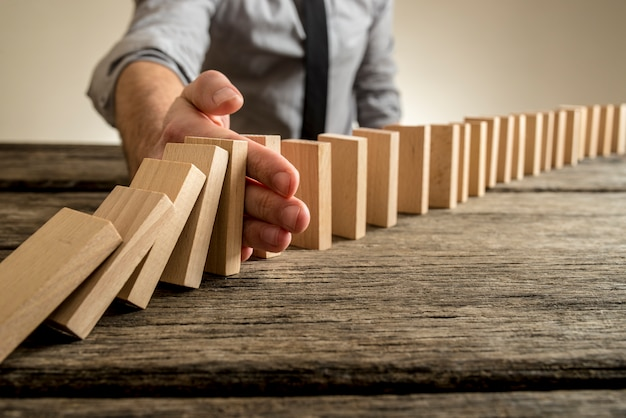 Uomo che ferma l'effetto domino sulla tavola di legno
