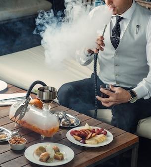 Uomo che fuma narghilè di frutta dalla pipa nella sala shisha