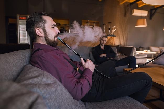 Uomo che fuma narghilè su un divano