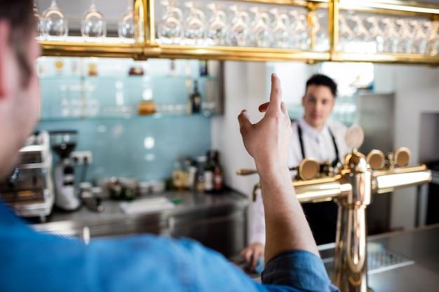 Uomo che gesturing mentre parla con il barista