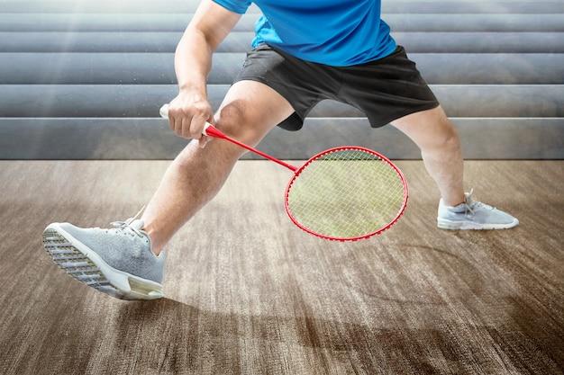 Uomo che gioca a badminton con la racchetta da badminton