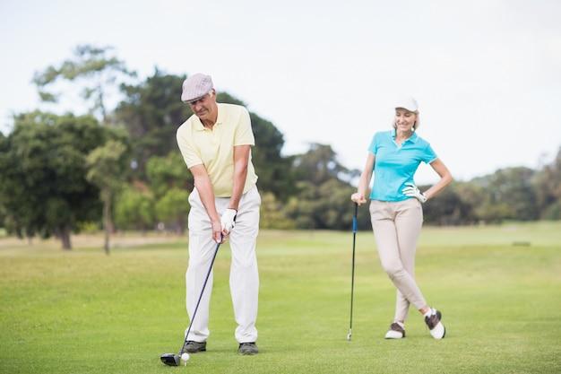 Uomo che gioca a golf mentre facendo una pausa donna