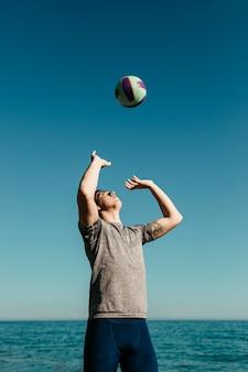 Uomo che gioca a pallavolo in spiaggia
