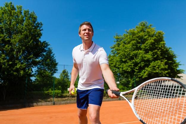 Uomo che gioca a tennis sulla corte all'aperto