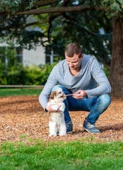 Uomo che gioca con shih tzu cucciolo all'aperto, addestramento del cane nel parco